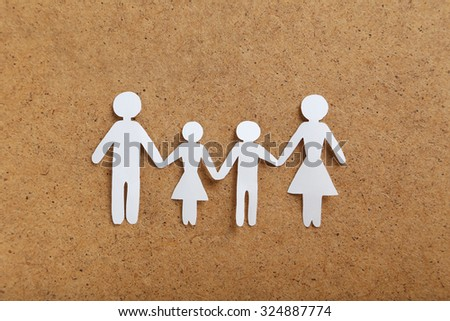 Happy paper family on brown background - stock photo