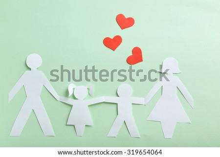 Happy paper family on green background - stock photo
