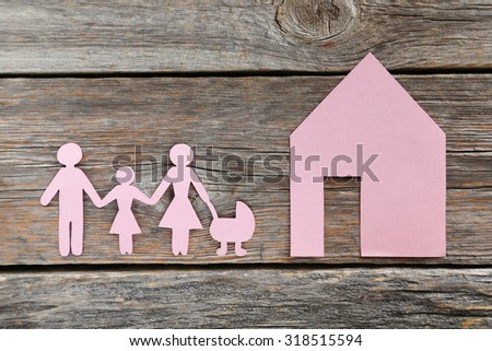 Happy paper family on grey wooden background - stock photo