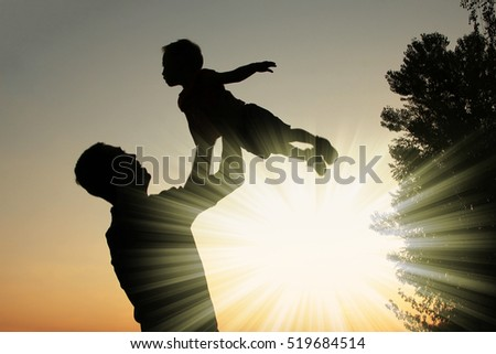 happy parent father with baby silhouette in a park on the nature of the sunset