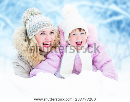 Happy parent mother and kid lying in snow outdoor - stock photo