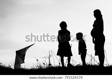 Happy parent with children playing on nature summer silhouette