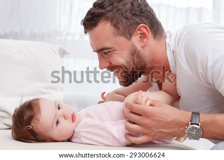Happy parenthood. Cute little child lying on sofa and looking aside with father touching the baby. - stock photo