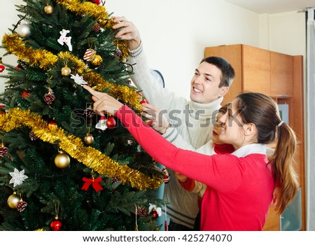 Happy parents and baby girl decorating Christmas tree - stock photo