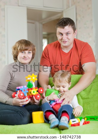 Happy parents and child plays with meccano set - stock photo