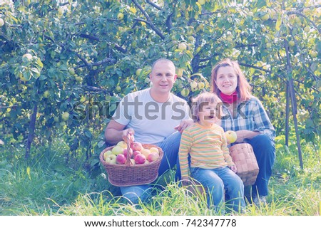 Happy parents and child with baskets of harvested apples in garden