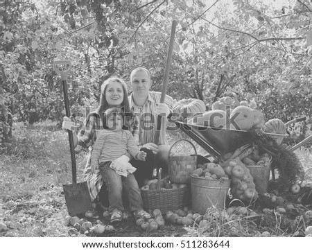 Happy parents and child with  harvested vegetables in garden
