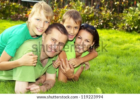 happy parents and children lie on the green grass