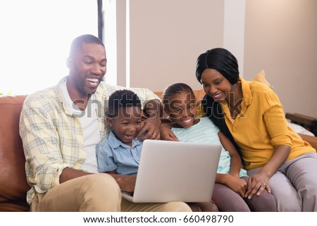 Happy parents and children using laptop while sitting on sofa at home
