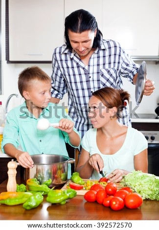 Happy parents and son cooking veggie lunch together in home kitchen