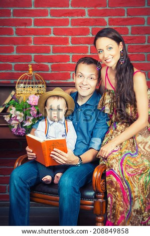 Happy parents and son reading a book, family leisure - stock photo
