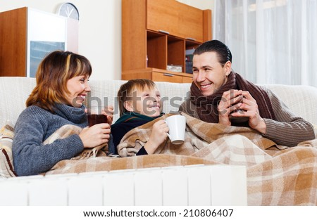 Happy parents and teenage son warming near warm heater in home