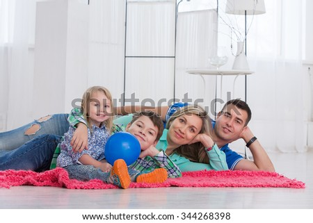 Happy parents and their children laughing on the floor in a bright room - stock photo
