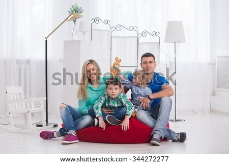 Happy parents and their children, sitting on a red couch in white interior