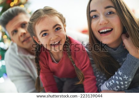 Happy parents and their cute daughter with pigtails laughing - stock photo