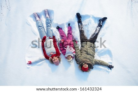 Happy parents and their daughter having fun in snowdrift - stock photo