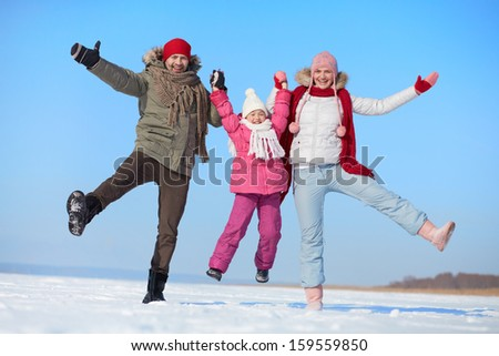 Happy parents and their daughter having fun in winter - stock photo