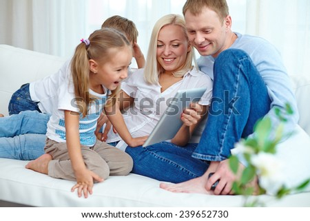 Happy parents and their two children resting on sofa with touchpad - stock photo