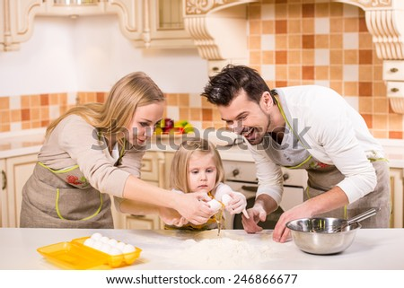 Happy parents and their young daughter are cooking, baking cakes in home kitchen.