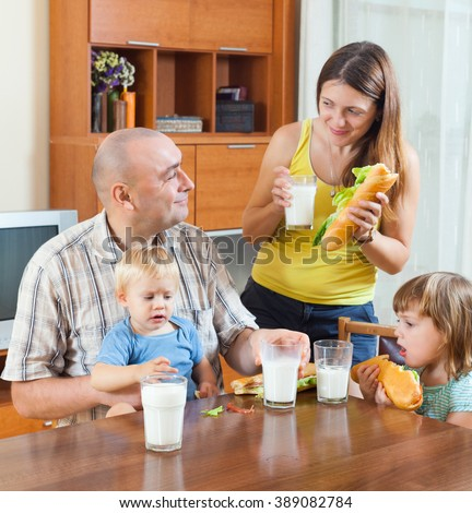 Happy parents and two children having lunch with sandwiches at the table - stock photo