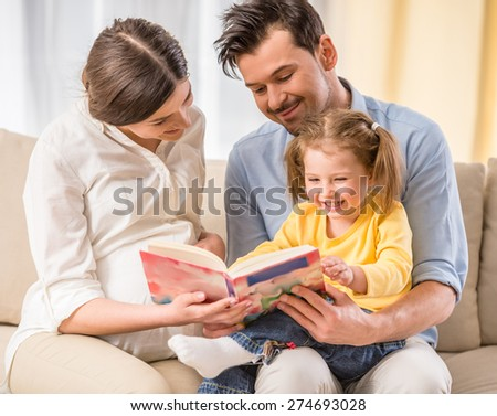 Happy parents are reading a book their kid girl. - stock photo