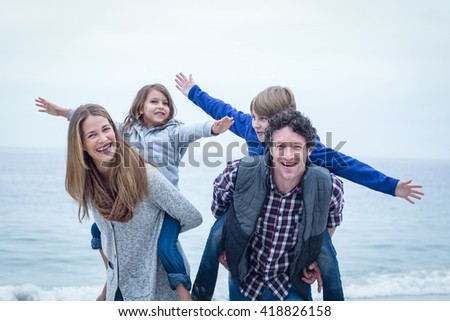 Happy parents carrying children and enjoying at sea shore - stock photo