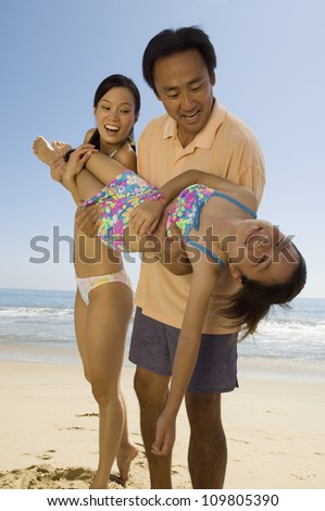 Happy parents carrying daughter on beach - stock photo
