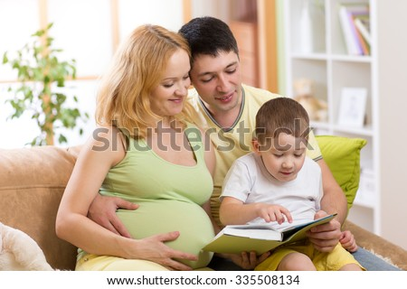 Happy parents - dad and pregnant mom reading book to child together on couch in home
