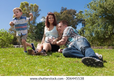 Happy parents expecting baby and enjoying sunny day with their active son in the park during sunny summer day. - stock photo