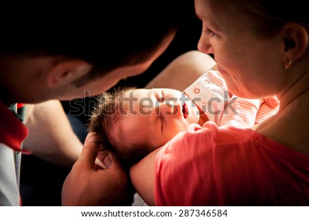 Happy parents holding their newborn baby girl - stock photo