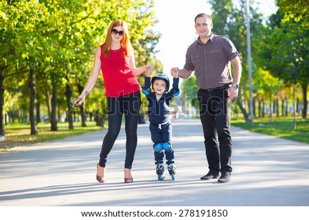 Happy parents holding their son riding on roller skates