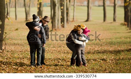 Happy parents hugging their children during foliage. Mother hugging his son and mother hugging her daughter.