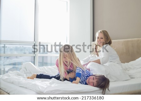 Happy parents looking at playful children in bedroom - stock photo