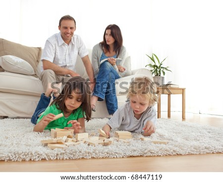 Happy parents on the sofa looking at their children playing on the floor at home
