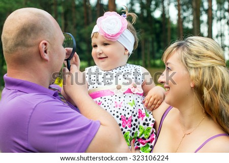 Happy parents playing with a baby in nature - stock photo