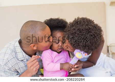 Happy parents playing with baby girl on bed together at home in the bedroom - stock photo