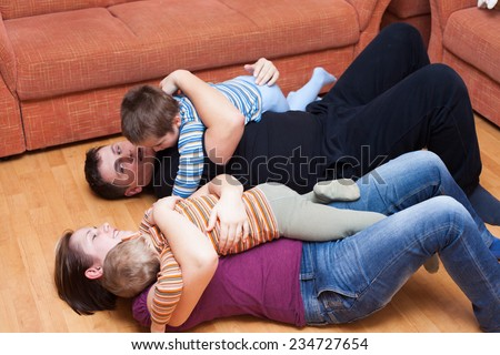 Happy parents playing with children at home - stock photo