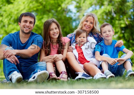 Happy parents posing with three children