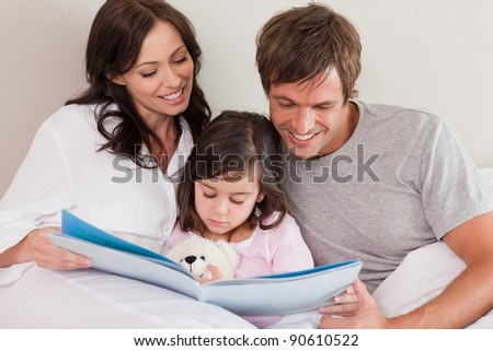 Happy parents reading a story to their daughter in a bedroom - stock photo