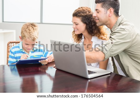 Happy parents showing son how to use tablet pc at home in kitchen - stock photo