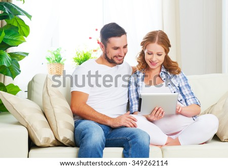 Happy parents waiting pregnant mom and dad with tablet computer on sofa at home
