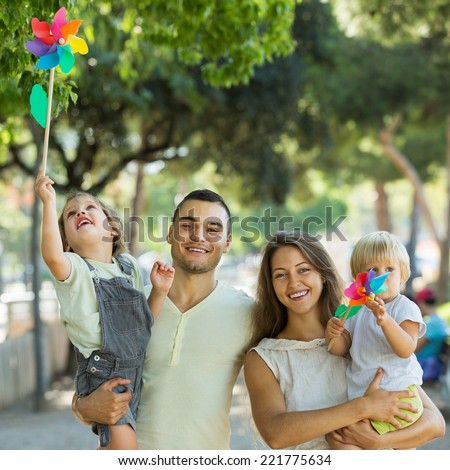 Happy parents walking with children on vacation day at park - stock photo