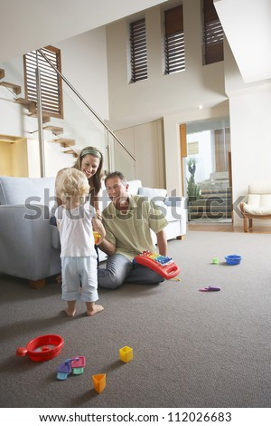 Happy parents watching daughter playing with toy at home