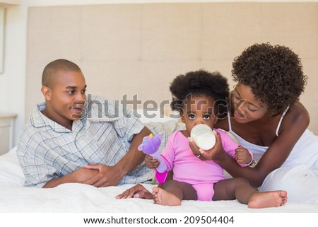 Happy parents with baby girl on their bed at home in the bedroom - stock photo