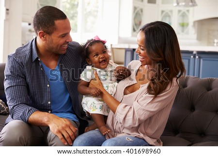 Happy parents with baby girl standing on mumâ??s knee - stock photo