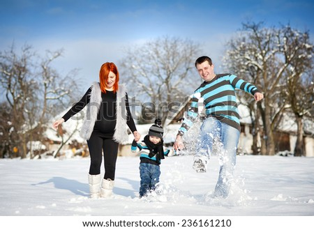 Happy parents with child having fun outside in snow - stock photo
