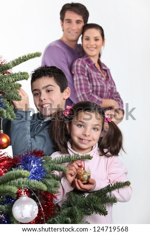 happy parents with children decorating Christmas tree - stock photo