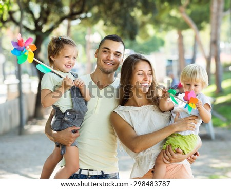 Happy parents with children playing windmills in park on sunny day