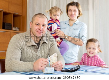 Happy parents with daughters counting money after salary. Focus on man - stock photo
