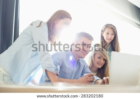 Happy parents with daughters using laptop at home - stock photo